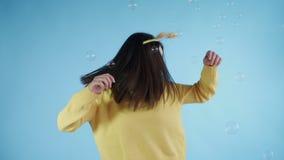 Η όμορφη νέα γυναίκα με το αστείο καπέλο είναι χορός με τις φυσαλίδες σαπουνιών σε ένα μπλε υπόβαθρο φιλμ μικρού μήκους