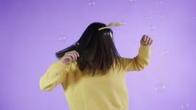 Η όμορφη νέα γυναίκα με το αστείο καπέλο είναι χορός με τις φυσαλίδες σαπουνιών σε ένα πορφυρό υπόβαθρο φιλμ μικρού μήκους