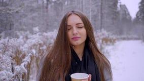 Η όμορφη νέα γυναίκα με το μίας χρήσης φλυτζάνι καφέ πίνει το τσάι ή τον καφέ υπαίθρια σε ένα χειμερινό πάρκο κίνηση αργή φιλμ μικρού μήκους