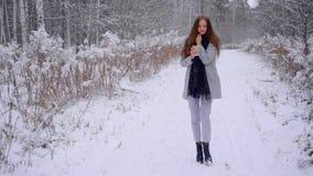 Η όμορφη νέα γυναίκα με το μίας χρήσης φλυτζάνι καφέ περπατά και πίνει το τσάι ή τον καφέ υπαίθρια σε ένα χειμερινό πάρκο αργός απόθεμα βίντεο
