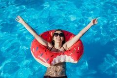 Η όμορφη νέα γυναίκα με το ρόδινο doughnut κύκλο έχει το υπόλοιπο στοκ φωτογραφίες