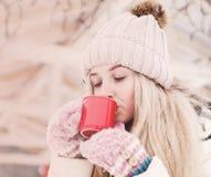 Η όμορφη νέα γυναίκα πίνει ένα καυτό κακάο υπαίθριο στοκ εικόνα