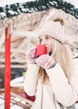Η όμορφη νέα γυναίκα πίνει ένα καυτό κακάο υπαίθριο στοκ φωτογραφία
