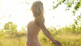 Η όμορφη νέα γυναίκα περπατά σε ένα ελαφρύ φόρεμα στα ξύλα στο ηλιοβασίλεμα φιλμ μικρού μήκους