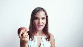 Η όμορφη νέα γυναίκα που τρώει τα κόκκινα χαμόγελα φρούτων μήλων και εξετάζει τη κάμερα η ανασκόπηση απομόνωσε το λευκό 4k, 3840x απόθεμα βίντεο