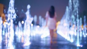 Η όμορφη νέα γυναίκα που φορά το φόρεμα περπατά στη φωτισμένη πηγή το βράδυ, σε αργή κίνηση φιλμ μικρού μήκους