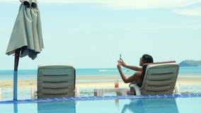 Η όμορφη νέα γυναίκα που χρησιμοποιεί το τηλέφωνό της παίρνει την εικόνα στον αργόσχολο παραλιών ενώ πάρτε μια ηλιοθεραπεία 3840x απόθεμα βίντεο