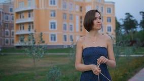 Η όμορφη νέα γυναίκα σε ένα μπλε φόρεμα, πηγαίνει στη tratuary διασκέδαση να συναντήσει το σύζυγό της φιλμ μικρού μήκους