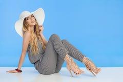 Η όμορφη νέα γυναίκα σε Jumpsuit, το άσπρο καπέλο ήλιων και τα υψηλά τακούνια κάθεται στο πάτωμα Στοκ Εικόνα