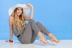 Η όμορφη νέα γυναίκα σε Jumpsuit, το άσπρο καπέλο ήλιων και τα υψηλά τακούνια κάθεται στο πάτωμα Στοκ εικόνα με δικαίωμα ελεύθερης χρήσης