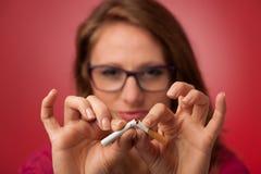 Η όμορφη νέα γυναίκα σπάζει ένα τσιγάρο ως χειρονομία για το εγκαταλειμμένο s Στοκ φωτογραφίες με δικαίωμα ελεύθερης χρήσης