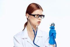 Η όμορφη νέα γυναίκα στα γυαλιά και στην ιατρική εσθήτα επιδέσμου κρατά ένα στηθοσκόπιο απομονωμένο στο λευκό υπόβαθρο, γιατρός,  Στοκ Εικόνα