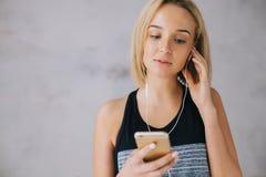 Η όμορφη νέα γυναίκα στην αθλητικά ένδυση και τα ακουστικά ακούει τη μουσική χρησιμοποιώντας ένα smartphone Στοκ φωτογραφίες με δικαίωμα ελεύθερης χρήσης
