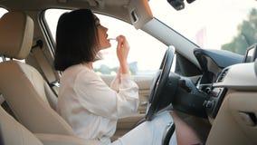 Η όμορφη νέα γυναίκα στον κομψό επιχειρησιακό ιματισμό που ισχύει makeup στο αυτοκίνητο που χρησιμοποιεί τον καθρέφτη για να εφαρ απόθεμα βίντεο
