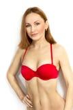 Η όμορφη νέα γυναίκα στο κόκκινο εσώρουχο σε ένα άσπρο υπόβαθρο Στοκ Φωτογραφίες
