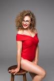 Η όμορφη νέα γυναίκα στο κόκκινο εσώρουχο σωμάτων θέτει καθμένος στην καρέκλα σε ένα γκρίζο υπόβαθρο Στοκ Εικόνες