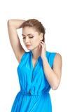 Η όμορφη νέα γυναίκα στο μπλε φόρεμα αύξησε τα χέρια της επάνω και κοιτάζοντας κάτω Στοκ Φωτογραφία