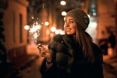 Η όμορφη νέα γυναίκα στο παλτό γουνών που κρατά ένα sparkler απολαμβάνει τη διάθεση χειμερινών Χριστουγέννων στην παλαιά χιονώδη  στοκ φωτογραφίες με δικαίωμα ελεύθερης χρήσης