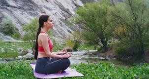 Η όμορφη νέα γυναίκα στο χαλί στη μέση της φύσης με τη γιόγκα άσκησης τοπίων που έχει μια περισυλλογή θέτει με φιλμ μικρού μήκους