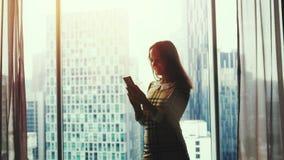 Η όμορφη νέα γυναίκα υπερασπίζεται το έξυπνο τηλέφωνο χρήσεων παραθύρων στο υπόβαθρο του καταπληκτικού ηλιοβασιλέματος και της θο φιλμ μικρού μήκους