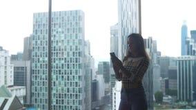 Η όμορφη νέα γυναίκα υπερασπίζεται το παράθυρο στο έξυπνο τηλέφωνο χρήσεων aparment στο υπόβαθρο της αστικής πόλης 3840x2160 απόθεμα βίντεο