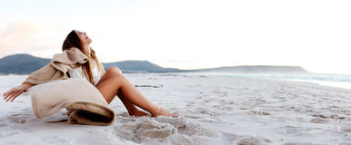 Η όμορφη νέα γυναίκα χαλαρώνει στην παραλία στοκ φωτογραφίες