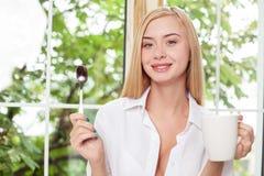 Η όμορφη νέα γυναίκα χαλαρώνει στο windowsill Στοκ Φωτογραφίες