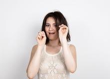 Η όμορφη νέα γυναίκα brunette σε μια τοποθέτηση φορεμάτων δαντελλών και εκφράζει τις διαφορετικές συγκινήσεις τα χέρια του κοριτσ Στοκ Φωτογραφία