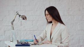 Η όμορφη νέα επιχειρηματίας γράφει τις σημειώσεις απόθεμα βίντεο