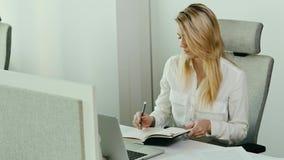 Η όμορφη νέα επιχειρηματίας εξετάζει το ημερολόγιο φιλμ μικρού μήκους