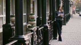 Η όμορφη νέα επιχειρηματίας χρησιμοποιεί τη συσκευή ταμπλετών στην οδό στο ηλιοβασίλεμα κοντά στο επιχειρησιακό ξενοδοχείο απόθεμα βίντεο