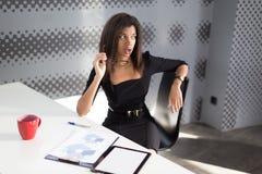 Η όμορφη νέα επιχειρησιακή κυρία στη μαύρη ισχυρή ακολουθία κάθεται στον πίνακα γραφείων Στοκ Εικόνες