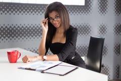 Η όμορφη νέα επιχειρησιακή κυρία στη μαύρη ισχυρή ακολουθία κάθεται στον πίνακα γραφείων Στοκ Φωτογραφία