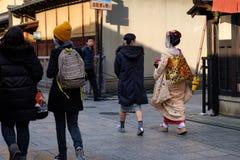Η όμορφη νέα ιαπωνική Maiko με το άσπρο makeup και το παραδοσιακό κιμονό που περπατούν τις οδούς του Κιότο φ στοκ εικόνες