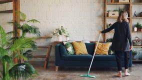 Η όμορφη νέα κυρία ακούει τη μουσική μέσω των ασύρματων ακουστικών και κάνει τα οικιακά καθαρίζοντας το πάτωμα με τη σφουγγαρίστρ απόθεμα βίντεο