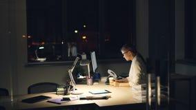 Η όμορφη νέα κυρία απασχολείται στις υπερωρίες χρησιμοποιώντας τον υπολογιστή που βγάζει αργά τη νύχτα έπειτα τα γυαλιά και το τρ απόθεμα βίντεο
