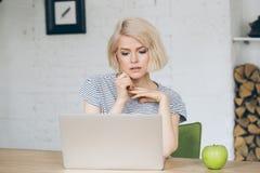 Η όμορφη νέα κυρία κάθεται μπροστά από ένα lap-top Apple εκτός από την Στοκ εικόνες με δικαίωμα ελεύθερης χρήσης