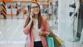 Η όμορφη νέα κυρία μιλά στο κινητό τηλέφωνο περπατώντας στις μόνες φέρνοντας τσάντες εγγράφου λεωφόρων αγορών Νέος ιματισμός επάν απόθεμα βίντεο