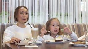 Η όμορφη νέα μητέρα και λίγη κόρη τρώνε το κέικ μαζί σε έναν άνετο καφέ απόθεμα βίντεο