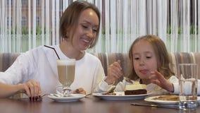 Η όμορφη νέα μητέρα και λίγη κόρη τρώνε το κέικ μαζί σε έναν άνετο καφέ φιλμ μικρού μήκους
