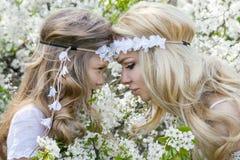 Η όμορφη νέα μητέρα με την κόρη της έντυσε την άνοιξη τα ενδύματα και τα στεφάνια των λουλουδιών Στοκ εικόνες με δικαίωμα ελεύθερης χρήσης