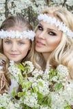 Η όμορφη νέα μητέρα με την κόρη της έντυσε την άνοιξη τα ενδύματα και τα στεφάνια των λουλουδιών Στοκ φωτογραφία με δικαίωμα ελεύθερης χρήσης