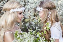 Η όμορφη νέα μητέρα με την κόρη της έντυσε την άνοιξη τα ενδύματα και τα στεφάνια των λουλουδιών Στοκ Εικόνα