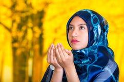 Η όμορφη νέα μουσουλμανική γυναίκα που φορά το μπλε χρωμάτισε hijab, αντιμετωπίζοντας τη κάμερα που διπλώνει τα χέρια εκτελώντας  Στοκ Εικόνες