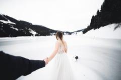 Η όμορφη νέα νύφη γυναικών κρατά το χέρι ενός άνδρα στο υπόβαθρο των βουνών Με ακολουθήστε στοκ εικόνα