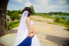 Η όμορφη νέα νύφη γυναικών κρατά το χέρι ενός άνδρα υπαίθρια Με ακολουθήστε στοκ εικόνες με δικαίωμα ελεύθερης χρήσης