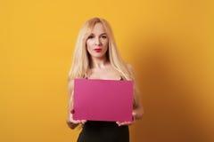 Η όμορφη νέα ξανθή γυναίκα κρατά το κενό σημάδι πινάκων στο κίτρινο υπόβαθρο Στοκ Εικόνες