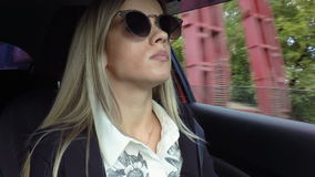 Η όμορφη νέα ξανθή γυναίκα οδηγεί το βίντεο μήκους σε πόδηα αποθεμάτων αυτοκινήτων φιλμ μικρού μήκους