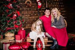 Η όμορφη νέα οικογένεια στο κόκκινο που έχει τη διασκέδαση μαζί για τις διακοπές Χριστουγέννων, που κάθονται σε ένα πάτωμα καθιστ Στοκ εικόνες με δικαίωμα ελεύθερης χρήσης