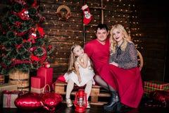 Η όμορφη νέα οικογένεια στο κόκκινο που έχει τη διασκέδαση μαζί για τις διακοπές Χριστουγέννων, που κάθονται σε ένα πάτωμα καθιστ Στοκ Φωτογραφίες